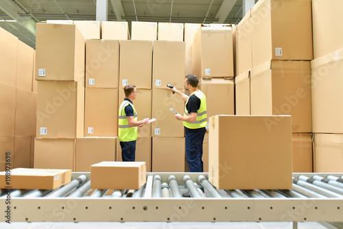 Logistiker arbeiten im Warenlager einer Spedition - Versand im Onlinehandel // Logisticians work in the warehouse of a forwarding agency - dispatch in online trade