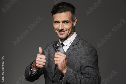 Caucasian office man in formal suit and tie demonstrating digital money in plastic credit card and showing thumb up, isolated over gray background