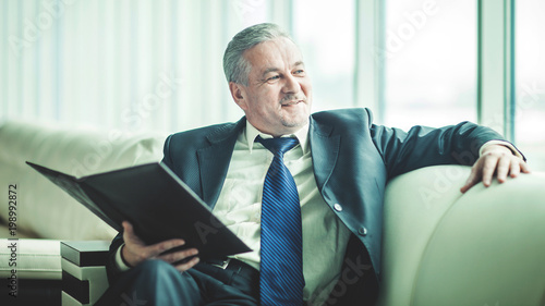 successful businessman is considering a new contract sitting on the sofa in the private office