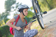 girl fixing bicycle tire outside
