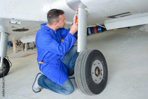 Fototapeta Mechanic working on aircraft landing gear