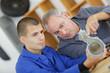 apprentice mechanic and mentor analyzing broken part
