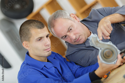apprentice mechanic and mentor analyzing broken part - 199013861