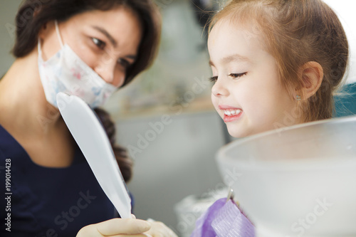 Little child looks at mirror on white polished teeth