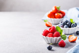 White ceramic bowl with fresh healthy berries. Raspberry, strawberry and blueberries. Copy space.