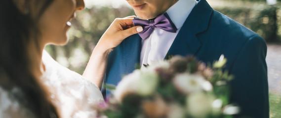Close-up image Bride Adjusting Groom's Tie, sun backlit. Bride put hand on groom's shoulder. Artwork