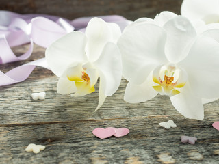 White orchid Phalaenopsis on a wooden background Pink ribbon heart