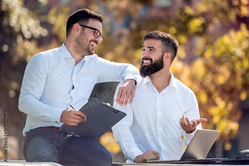 Two businessmen talking outdoors,having break.