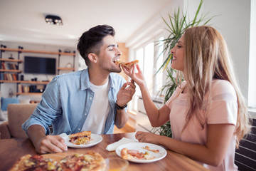 Young couple enjoying eating pizza at home