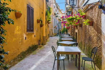 Cafe tables and chairs outside in old cozy street in the Positano town, Italy