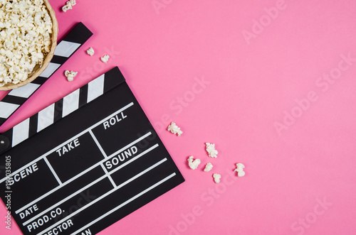 Fresh popcorn and movie clip isolated on pink background top view with copy space around products. Cinematic concept for blogs or design - 199035805