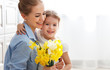 happy mother's day! child daughter   gives mother a bouquet of flowers to narcissus and gift - 199059404