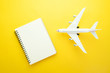 Flat lay design of travel concept with plane and blank notebook  on yellow background with copy space.