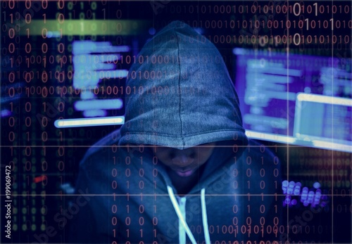Hacker in a hoody with tech background