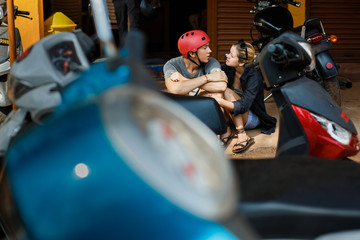 A guy and a girl are sitting on the ground next to a garage repair shop for motorbikes