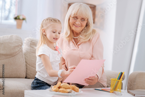Talented child. Cheerful positive aged woman holding a drawing and smiling while talking to her granddaughter