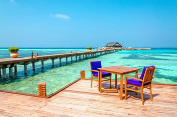 Tables and chairs in a wooden restaurant on stilts on the background of azure water and blue sky