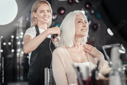 Foto op Plexiglas Kapsalon Great mood. Cheerful positive elderly woman looking at her reflection and smiling while being in a good mood