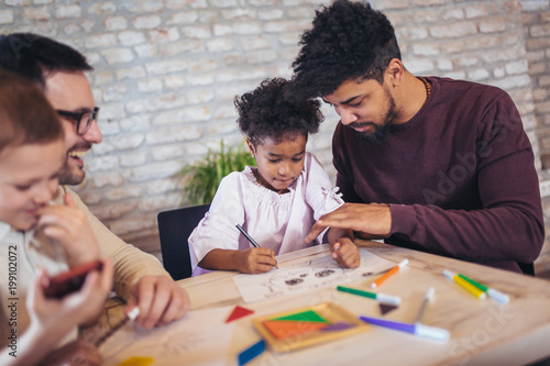 Two fathers play educational games with their children, having fun.