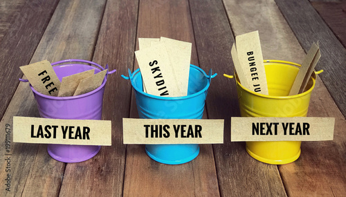 Conceptual and inspirational resolution wordings - 'Last year, this year and next year' written on sticky notes. With vintage styled background.