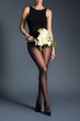 Young woman wearing black bodysuit and tights and holding bouquet of flowers on dark background