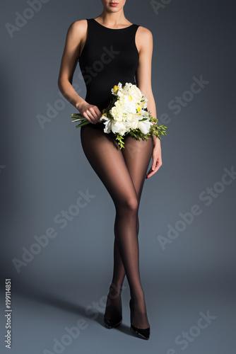 Młoda kobieta jest ubranym czarnego bodysuit, rajstopy i trzyma bukiet kwiaty na ciemnym tle