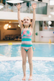 Little girl standing on the floor in a pool