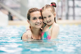 Young girl and her mother hugging in the pool.