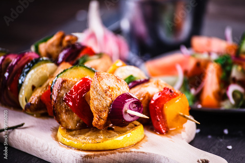 Kebabs - grilled meat with vegetables on wooden background - 199116003