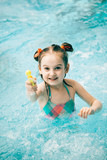Girl in a swimming pool with a water pistol