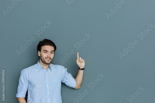 Look up. Cheerful positive creative man standing against grey background and smiling to you while pointing up with his finger