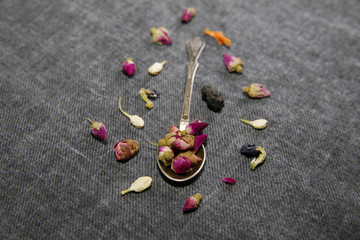Dry rose for tea in spoon on grey fabric