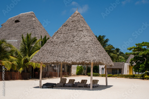 Keuken foto achterwand Tropical strand Bamboo hut with Beach bed among palm trees at perfect tropical coast fresh green palm trees around standing at the white sand beach and cloudless blue sky on a sunny day. Spa concept.