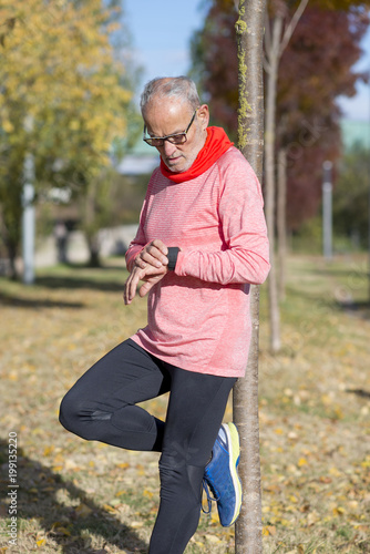 Poster Jogging Senior runner man resting at the park while monitoring his exercise