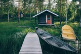 Traditional wooden hut. Finnish sauna on the lake and pier with fishing boats - 199143872