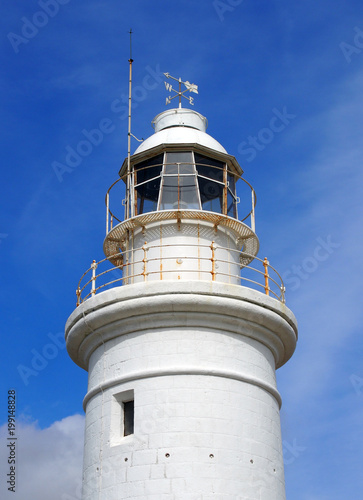 Fotobehang Cyprus the top of the old white historic lighthouse in paphos cyprus with blue sky