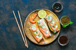 Spring rolls with shrimp in rice paper with various sauces. Rustic blue rusty background. Top view, copy space.