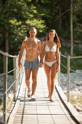 Active young couple on a bridge over alpine river on hot summer morning - 199152490