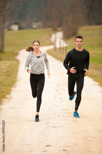 Aluminium Hardlopen Young veautiful couple runs on a path in park on autumn afternoon