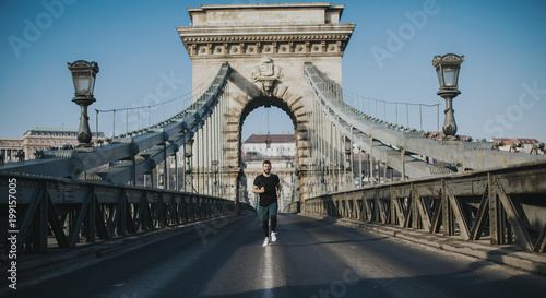 Young man running on Chain bridge in Budapest, Hungary - 199157005