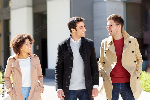 business, communication and people concept - office workers or friends talking on city street