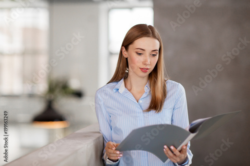 business, people and corporate concept - female office worker with folder - 199163249