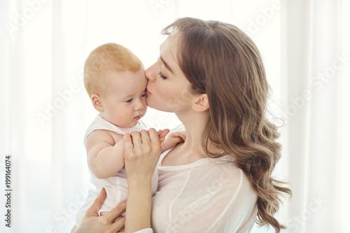 Matka z dzieckiem w ramionach gra w okno. Dzień Matki.