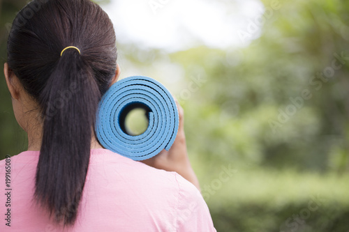 Fototapeta Young woman holding a blue yoga mat in exercise class for a sport and healthy concept
