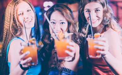 Group of party people - women with cocktails in a bar or club having fun showing their drinks