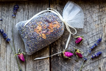 bag with wild roses petals and dried lavender flowers on wooden, vintage background -  fragrance to the wardrobe