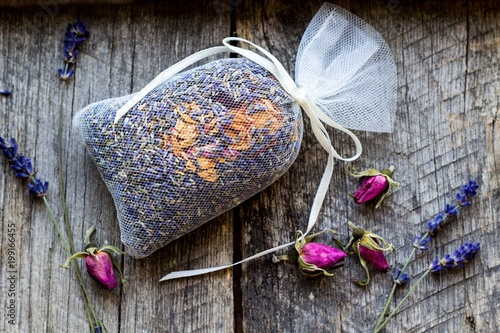 bag with wild roses petals and dried lavender flowers on wooden, vintage background -  fragrance to the wardrobe - 199166455