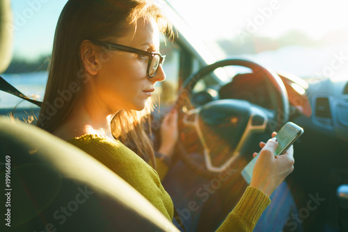 Woman in glasses uses a smartphone while driving a car at sunset