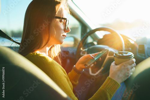 Woman using smartphone and drinking coffee while sitting in a car