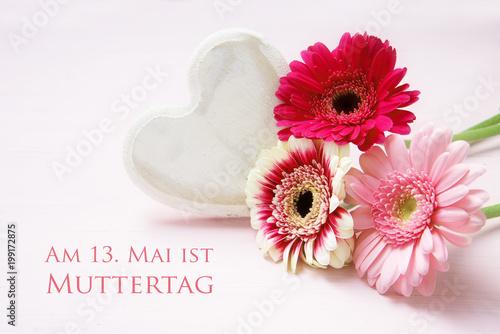 Aluminium Gerbera Rosa Gerbera Blumen und ein Herz aus Holz auf einem hellen Hintergrund, Text Am 13. Mai ist Muttertag